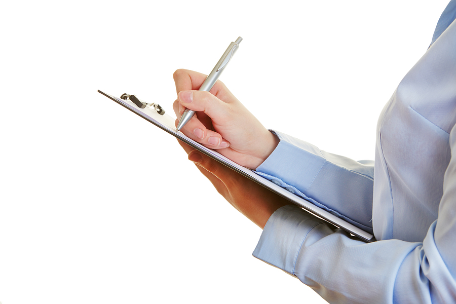 bigstock-Hand-holding-pen-and-checklist-48266159